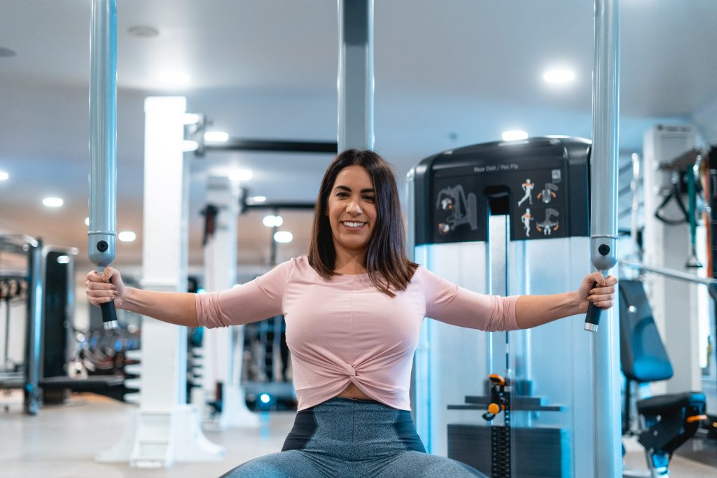Woman on chest fly machine